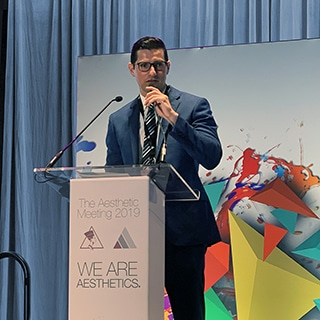 A photograph of Dr. Jason Roostaeian presenting at the Aesthetic Meeting ASAPS 2019