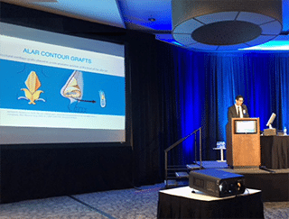A photo of Dr. Jason Roostaeian presenting a rhinoplasty lecture at the Dallas Rhinoplasty Meeting 2018