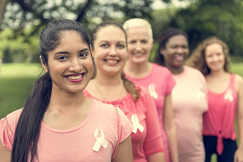 A photo of women in pink representing Dr. Jason Roostaeian's natural looking breast reconstruction