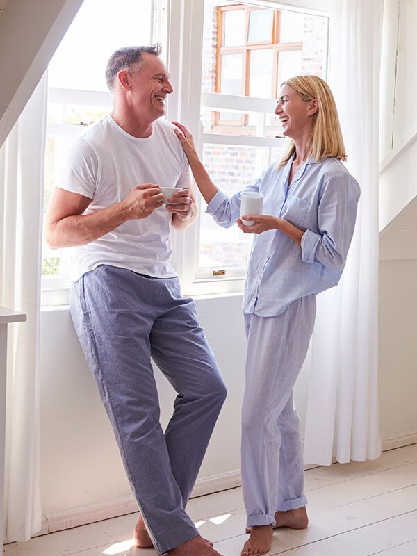 A photo of a middle aged couple in pajamas representing Dr. Jason Roostaeian's natural looking facelift surgery