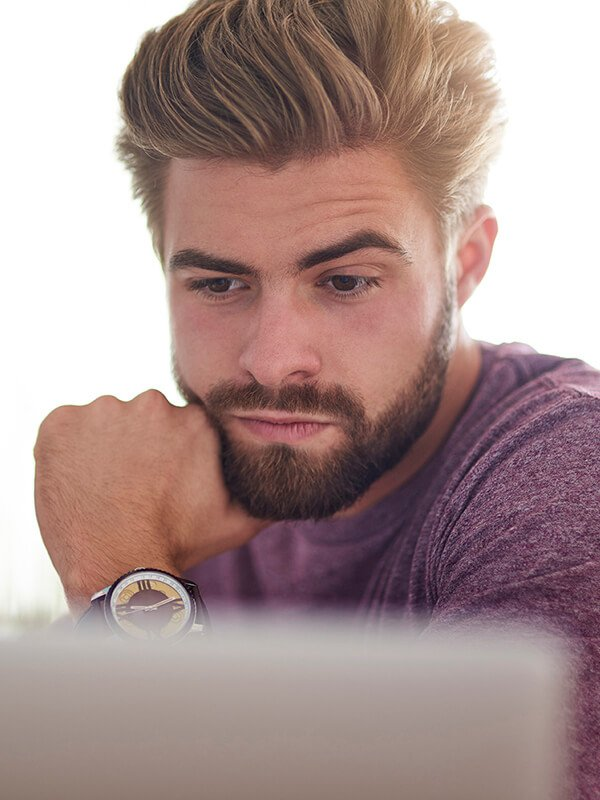 A photo of a man looking at a computer representing Dr. Jason Roostaeian's natural looking male cosmetic surgery service