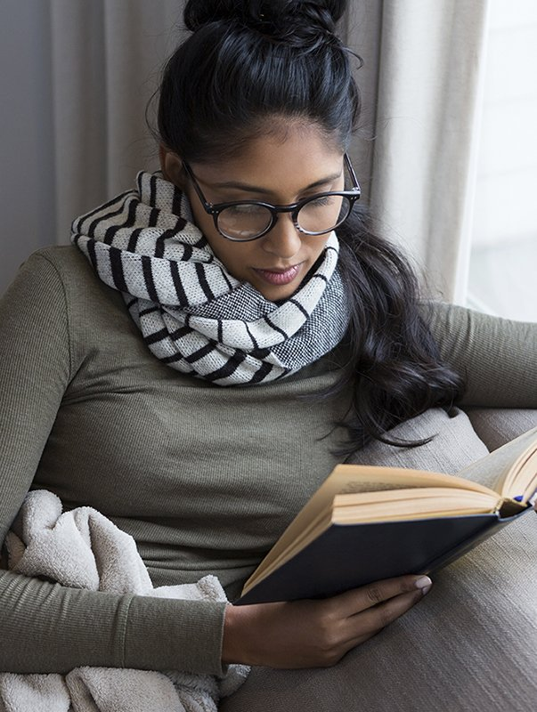 A woman reading a book representing Dr. Jason Roostaeian's natural looking tummy tuck recovery